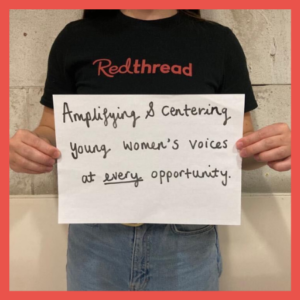 """A Young Women's Worker holding up a piece of paper that reads """"Amplifying and centring young women's voices at every opportunity"""""""