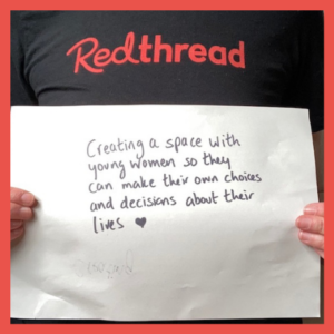 """A Young Women's Worker holding up a piece of paper that says """"Creating a space with young women so they can make their own choices and decisions about their lives."""""""