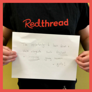 """A Young Women's Worker holding up a piece of paper reading """"The opportunity to learn from and work alongside such resilient and inspiring young women and girls."""""""